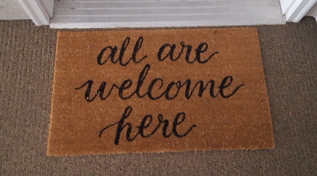 """""""All Are Welcome Here"""" door mat I found while passing out cards."""