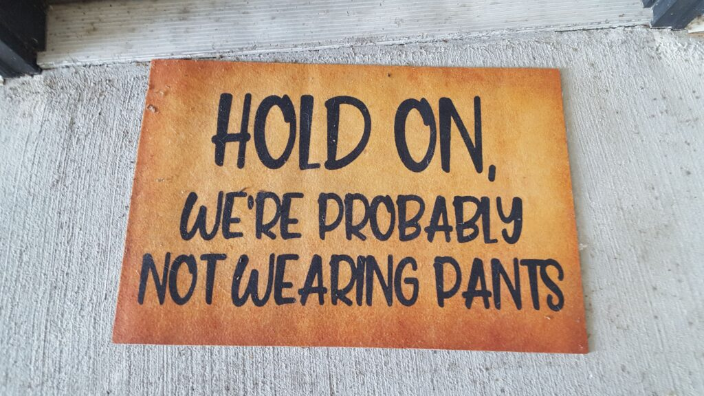 """Door mat, with the words """"Hold On, we're probably not wearing pants. From my experiment of passing out 2000 cards."""
