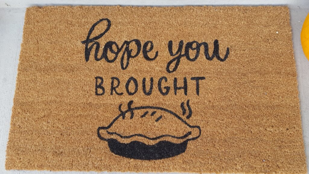 """Door mat with the words, """"Hope you brought pie."""" One that I encountered while passing out cards."""